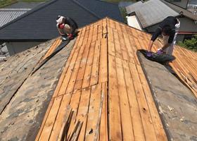 屋根の葺き替え工事作業の瓦の下の土や防水シート撤去画像
